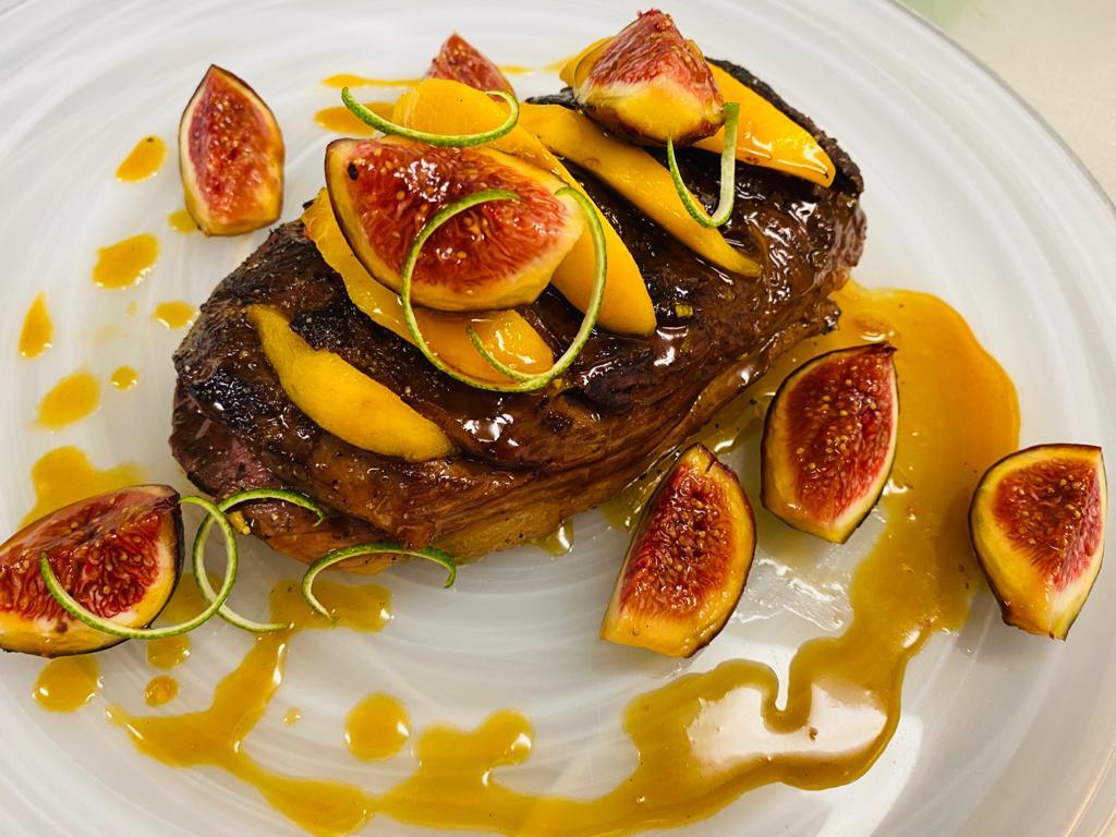 Magret de pato con salsa de naranja, melocotones e higos
